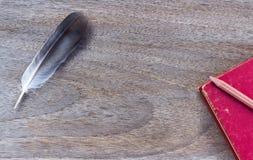 Gołębia piórko z książką i ołówkiem na drewnianym tekstury backgr Obrazy Stock