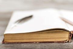 Gołębia piórko z książką i ołówkiem na drewnianym tekstury backgr Zdjęcia Stock