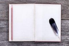 Gołębia piórko z książką i ołówkiem na drewnianym tekstury backgr Zdjęcie Royalty Free