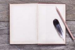 Gołębia piórko z książką i ołówkiem na drewnianym tekstury backgr Fotografia Royalty Free