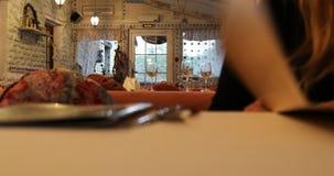 Gość kawiarnia egzamininuje menu, siedzi przy stołem zbiory wideo
