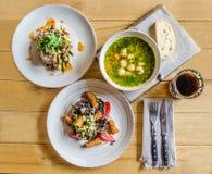 Gość restauracji: polewka z klopsikami, ziele, ciastka z serem, pomidory, ziele, sałatka z mięsem i ziele, chleb, szkło drin obrazy royalty free