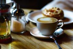 Gość wygodna kawiarnia, rozkazywać filiżanka cappuccino i waniliowy Donat, Cieszy się jej apetyt obrazy royalty free