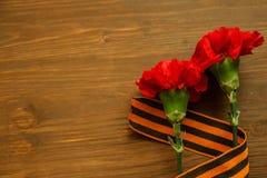 Goździk i George faborek na abstrakta światła tle kwitniemy 9 kalendarzowy dzień może czerwony zwycięstwo Jubileusz 70 rok Zdjęcie Stock