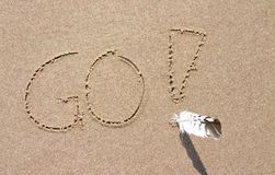 Go. Slogan GO written on sand with exclamation mark and real feather Royalty Free Stock Photography