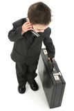 On The Go. Little business man with cellphone and briefcase Royalty Free Stock Image