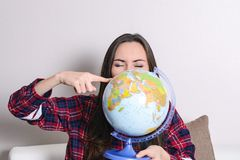 Go on an adventure. Fun woman dreaming about traveling around the world, spinning a globe and pointing at random country. Happy cu. Te brunette preparing for the Royalty Free Stock Image