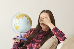 Go on an adventure. Fun woman dreaming about traveling around the world, twisted a globe and closes eyes. Happy cute brunette prep. Aring for the journey Stock Photography