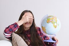 Go on an adventure. Fun woman dreaming about traveling around the world, twisted a globe and closes eyes. Happy cute brunette prep. Aring for the journey Stock Photo