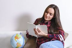 Go on an adventure. Pretty woman dreaming about traveling around the world, making notes in a diary with countries for travel. Hap. Py cute brunette preparing Stock Image