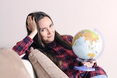 Go on an adventure. Woman dreaming about traveling around the world, looking in camera with globe in hand. Happy cute brunette pre. Paring for the journey Stock Photography