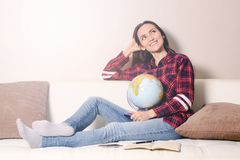 Go on an adventure. Woman dreaming about traveling around the world, looking at the globe in room of the house. Pretty girl study. Go on an adventure. Woman Stock Photo