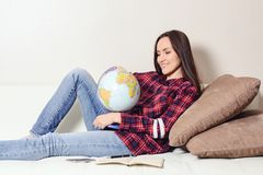 Go on an adventure. Woman dreaming about traveling around the world, looking at the globe in room of the house. Pretty girl study. Go on an adventure. Woman Royalty Free Stock Photos