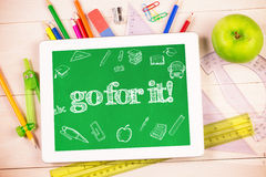 Go for it! against students desk with tablet pc. The word go for it! and education doodles against students desk with tablet pc Royalty Free Stock Photo