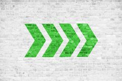 Go ahead green directional arrow signs pointing direction painted on a white gray brick wall signboard texture background royalty free stock photo