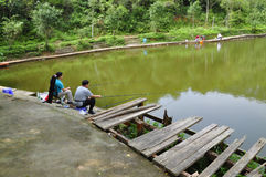 Go angling. Recreational anglers sitting by the lake at the weekend holiday Stock Photos