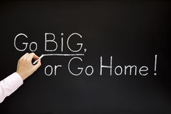 GO BIG concept. Hand writing GO BIG, OR GO HOME with white chalk on a blackboard Royalty Free Stock Photos