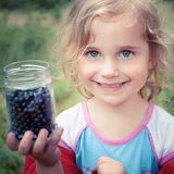 Go blueberry picking. Little girl holding a jar of blueberries Stock Photos