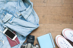 Go on board an adventure trip with camera, smart phone and more items, Flat lay on wood. Background Stock Photos