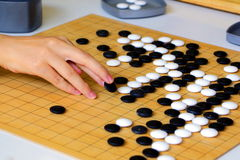 Go board game playing. A competitor is placing a marble piece on a Go board game royalty free stock image