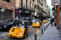 Go cars in Madrid, Spain. Tourist in a GoCar in the streets of Madrid. GoCar is a two-seater, 3 wheeled vehicle that runs with a 49cc size scooter engine for Stock Photo