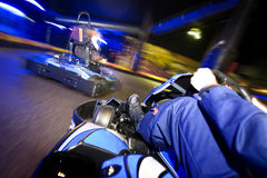 Go-cart in pursuit. Go-carts in pursuit on an indoor race track Stock Photos