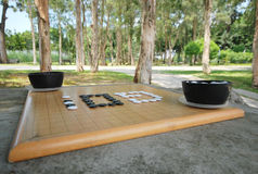Go Chess Game Set. A set of Go chess placed on a stone table in a serene quiet park Royalty Free Stock Photos