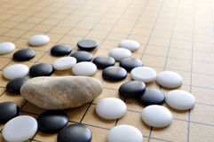 Go chess rule breaker. A piece of pebble intrudes a go chess game Royalty Free Stock Photography