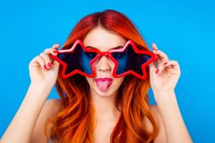 Go crazy! Young cheerful foxy with big funny star glasses and to. Ngue out is fooling around on the blue background Royalty Free Stock Images