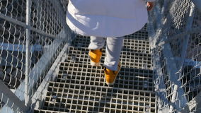 Go down the stairs - Human feet in yellow sneakers are going down the metal stairs of the bridge. View from behind stock footage