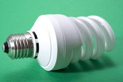 Go ecofriendly. A energy saver bulb on a green background royalty free stock photos