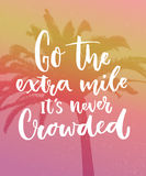 Go the extra mile, it`s never crowded. Motivation quote about progress and dreams on pink vintage background with palm. Silhouette. Inspirational typography Royalty Free Stock Images