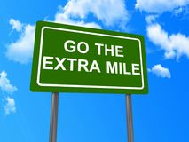 Go the extra mile sign. A green traffic style sign board with white text in upper case letters saying Go the extra mile seen against a blue sky with a few clouds royalty free illustration