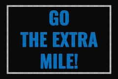 Go The Extra Mile text on dark screen. Tv effect royalty free illustration