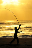Go Fishing in the Dawn. A lonely man angling at a beach in the dawn Stock Images