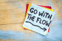 Go with the flow advice on sticky note. Go with the flow advice or reminder on a sticky note against grunge painted wood background Stock Photography