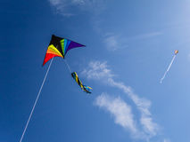 Go Fly A Kite!. Colorful delta wing kite with windsock tail flying against a deep blue sky.  Another kite in the distance.  Thin ribbon of some  light wispy Royalty Free Stock Photo