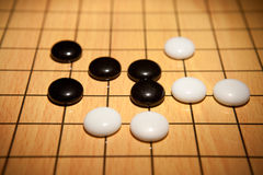 Go game. Black and white pieces on Go game board Stock Photos