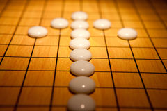 Go game. White arrows  on Go game board Royalty Free Stock Images