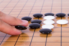 Go Game. Close up view of hand playing black and white stone pieces on Chinese go game board Royalty Free Stock Images