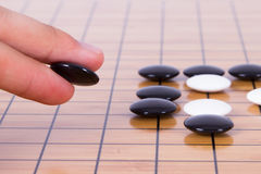 Go Game. Close up view of hand playing black and white stone pieces on Chinese go game board Stock Images
