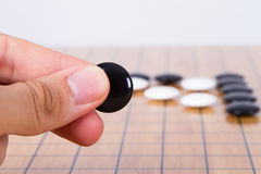 Go Game. Close up view of hand playing black and white stone pieces on Chinese go game board Royalty Free Stock Photo