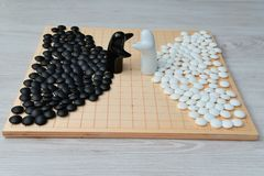 Go game pieces and two black and white figures. On go board Royalty Free Stock Photo