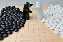 Go game pieces and two black and white figures. On go board Royalty Free Stock Images