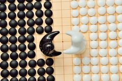 Go game pieces and two black and white figures. On go board Stock Image