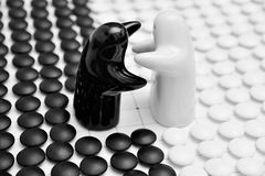 Go game pieces and two black and white figures. On go board Royalty Free Stock Image