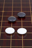 Go game playing on dark wood goban. Four stones during go game playing on dark wood goban Stock Images
