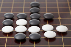 Go game playing by stones on wood board. Go game playing by stones on wood go board Royalty Free Stock Photos