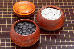 Go game stones in wooden bowl Stock Images