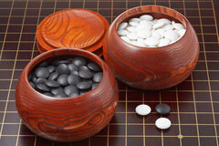 Go game stones and wooden bowls on wood board Stock Images
